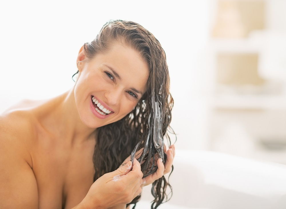 woman adding product to wet hair