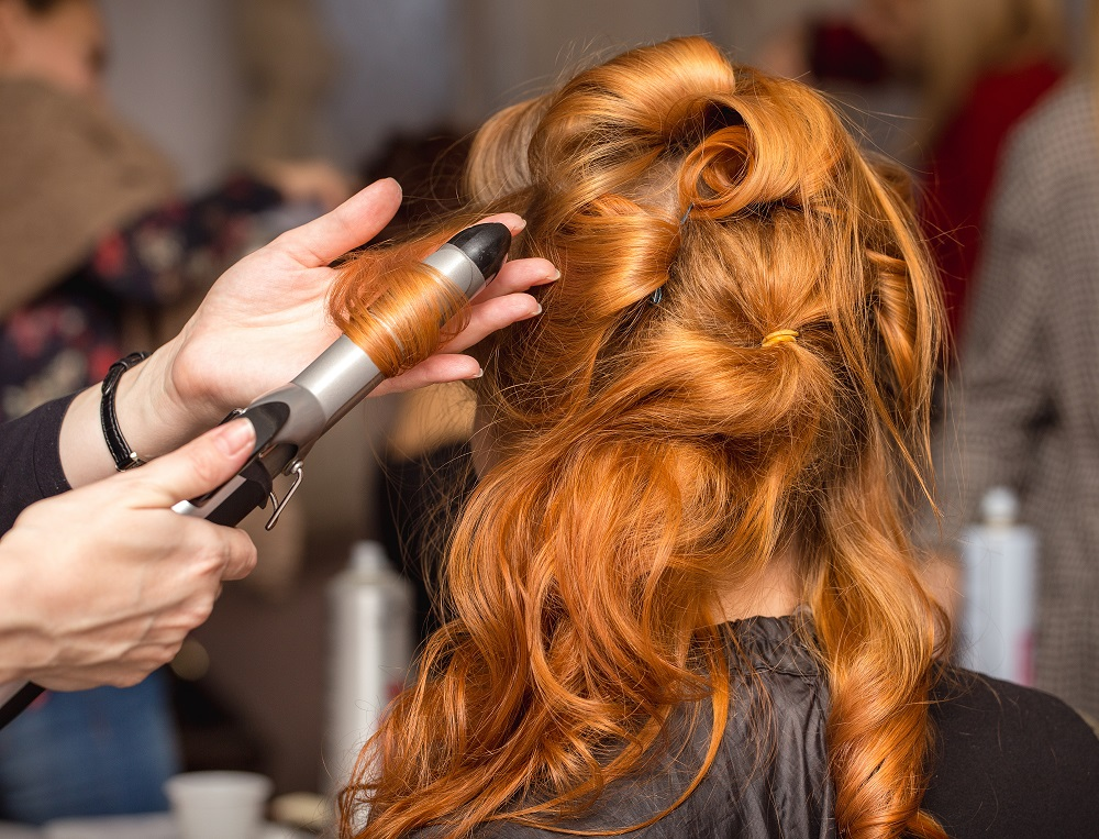 woman getting red hair curled