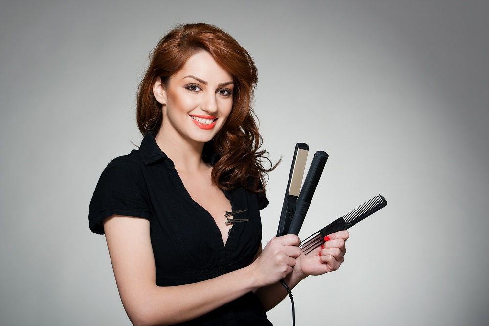 young woman holding comb and straightener