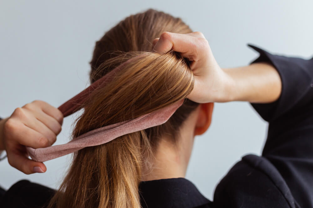 Woman tying ponytail