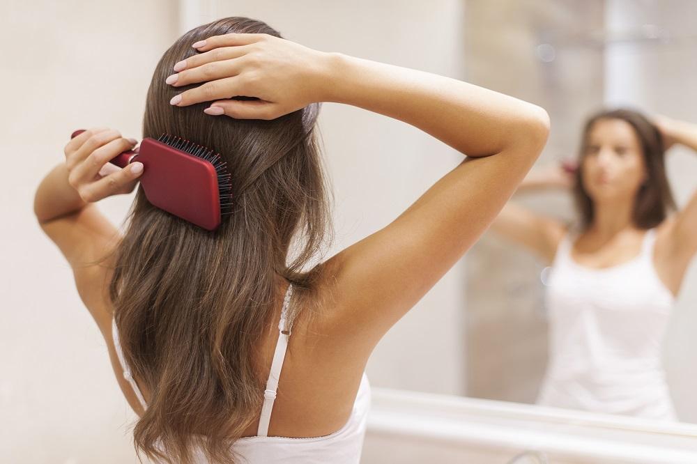 woman brushing hair with paddle brush
