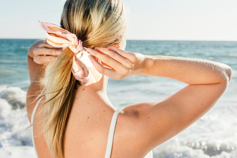 Woman doing hair on beach