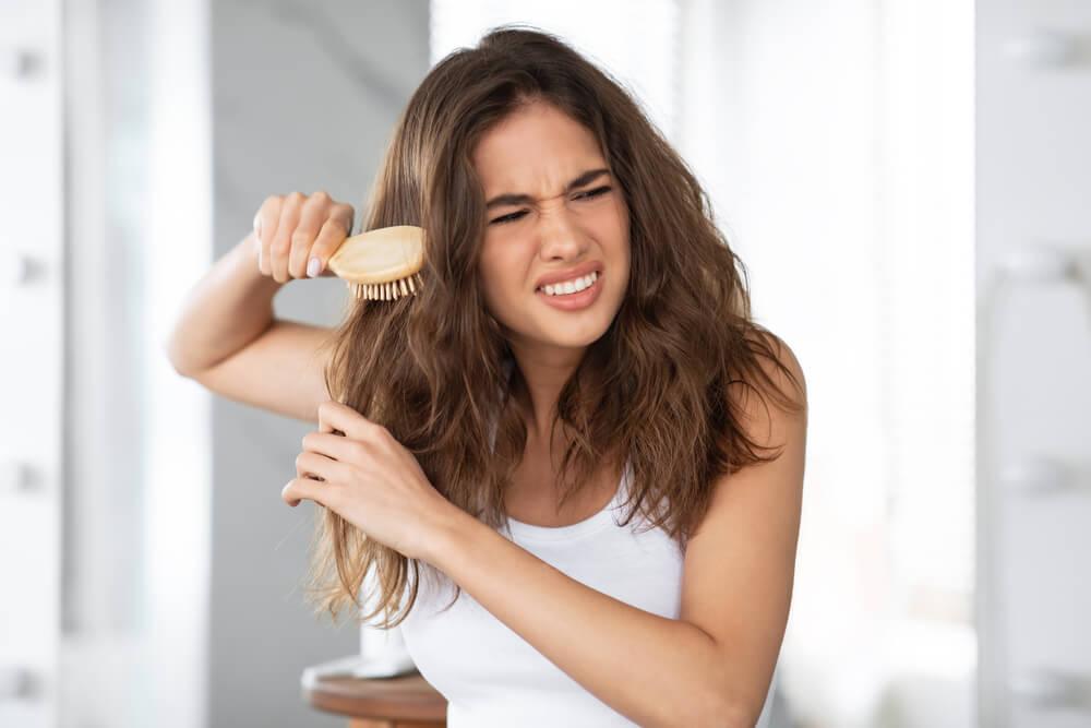 Woman brushing hair tangles