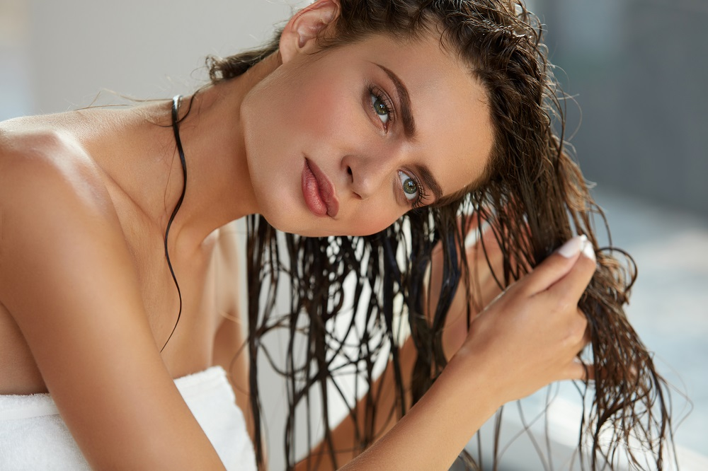 woman applying product to wet hair