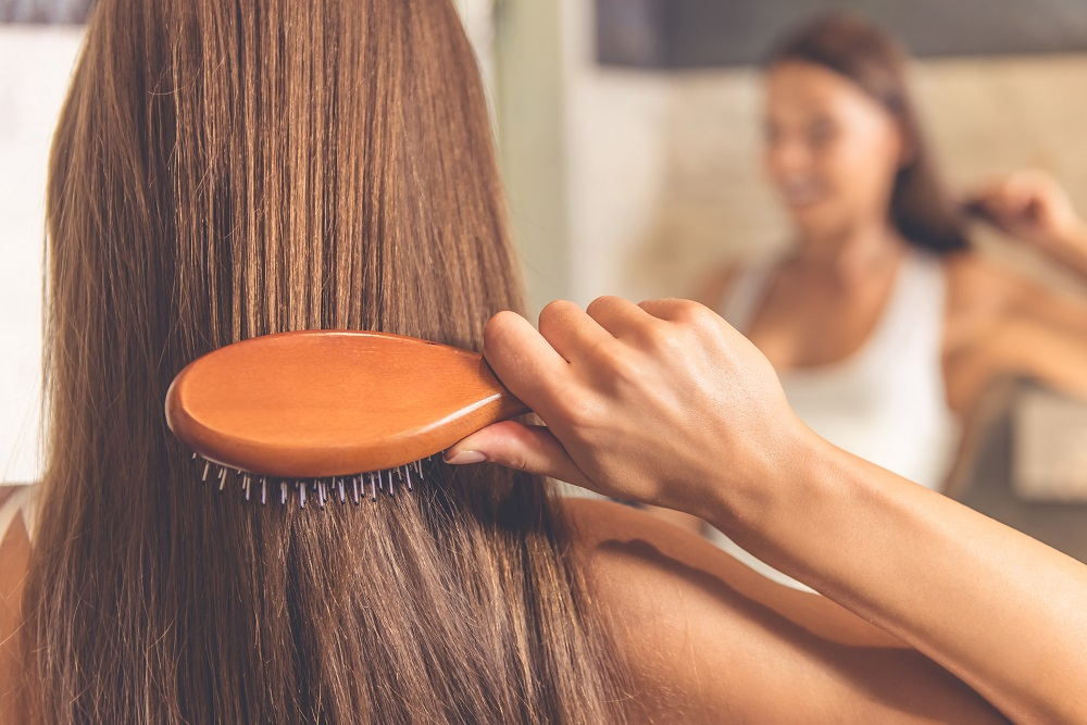 woman brushing hair with wooden brush