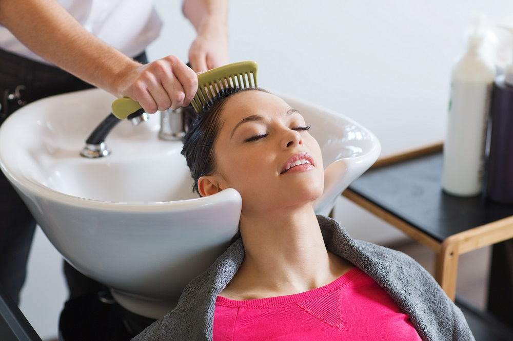 woman getting get hair combed with a wide tooth comb