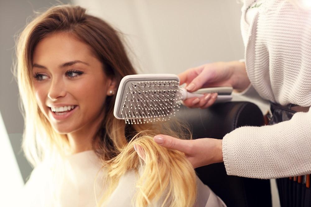 stylist brushing womans hair