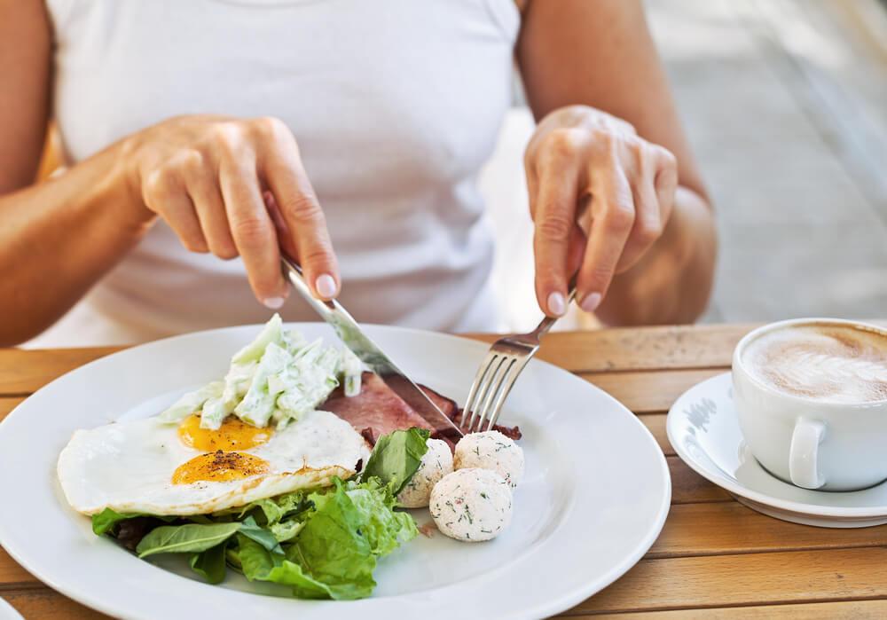 Woman eating eggs breakfast