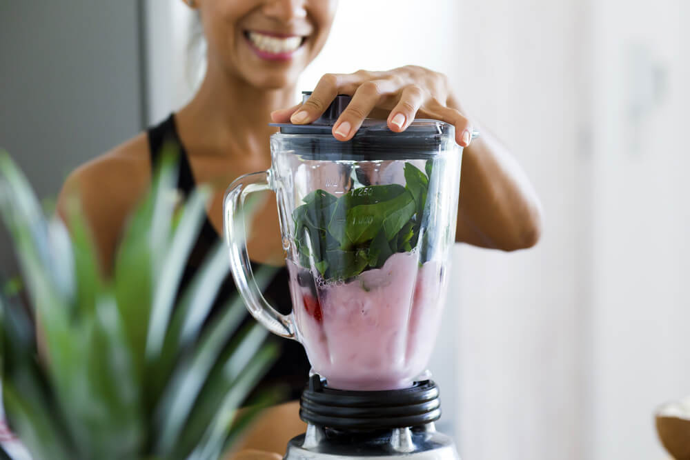 Woman making green and pink smoothie