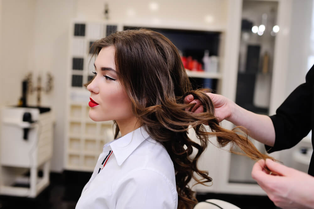 Hairstylist curling woman's hair