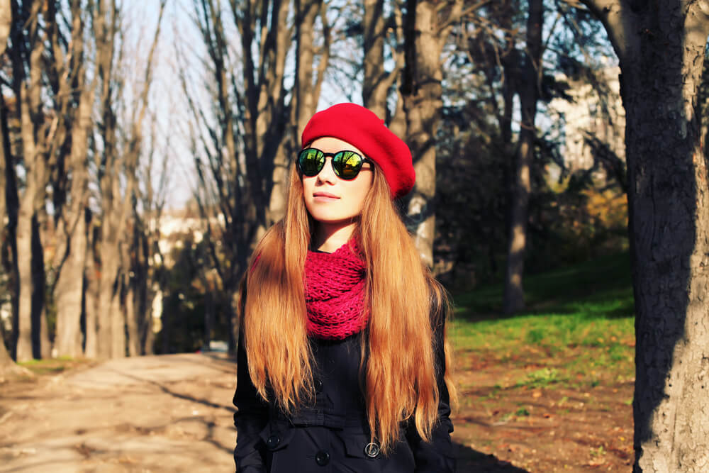 Fashionable woman with sunglasses and loose red beanie
