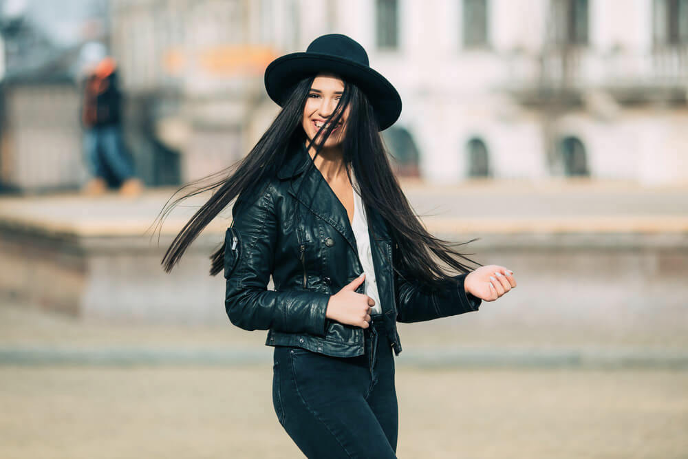 Happy young woman with long straight black hair smiling in the street