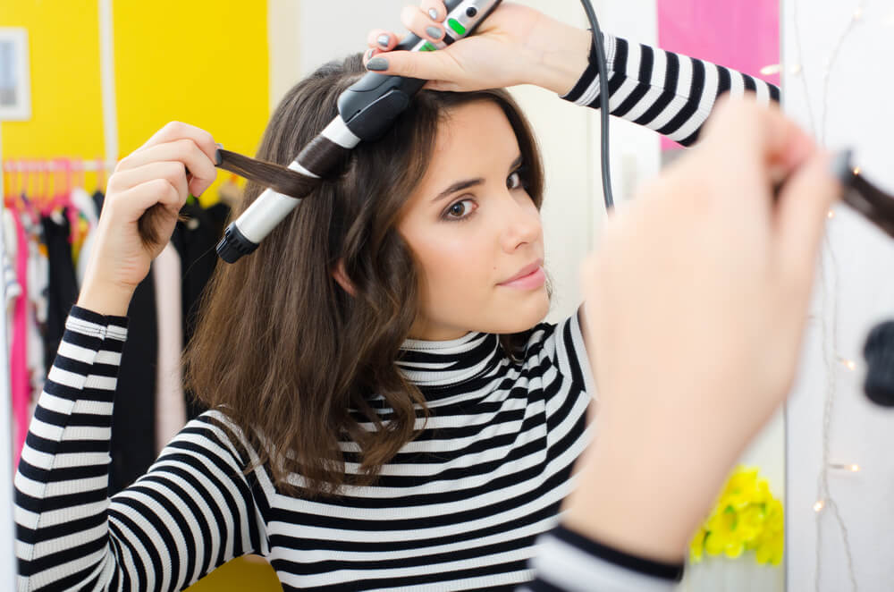 Young woman curling her hair with a styling tool
