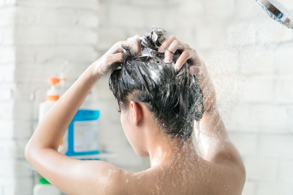 Unknown woman shampooing hair in the shower