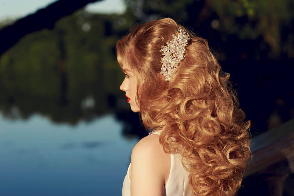 Side profile of woman with long curly blonde hair secured with a floral banana clip
