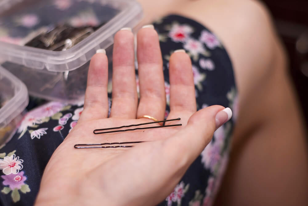 A couple of bobby pins in a female palm