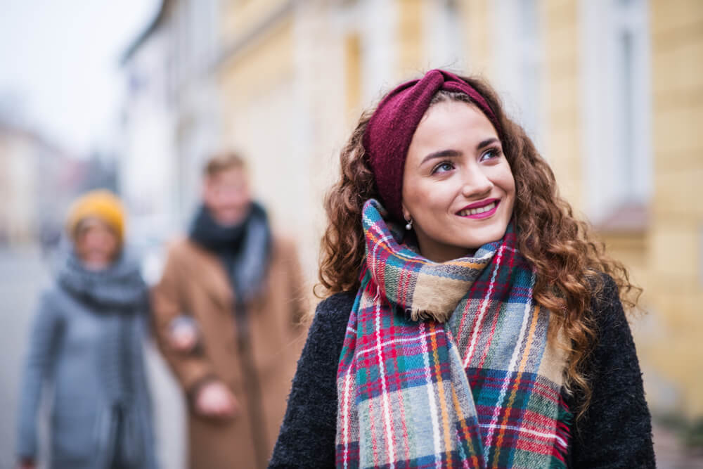 Happy smiling fashionable woman in winter with red headband and checkered scarf