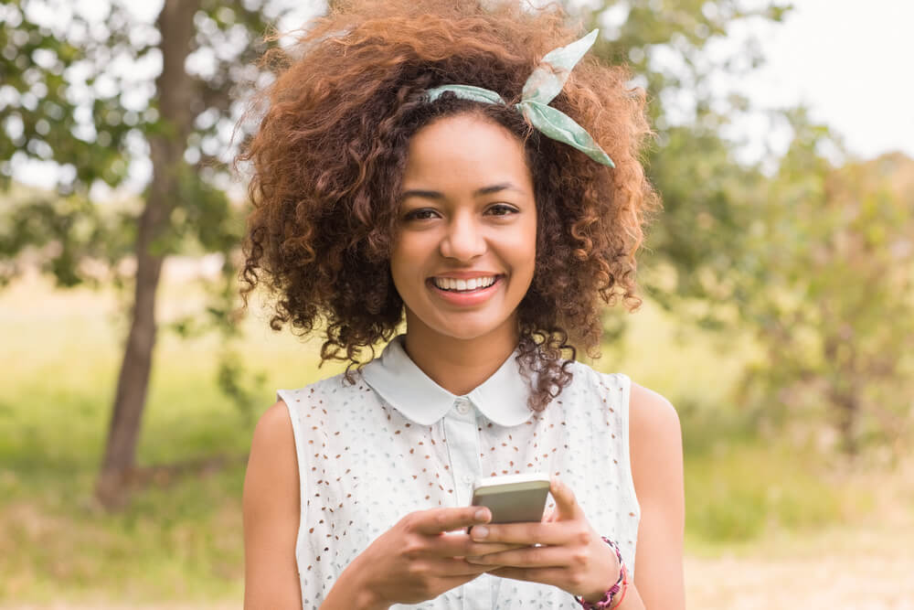 Happy smiling woman with headband, using her mobile phone in the park