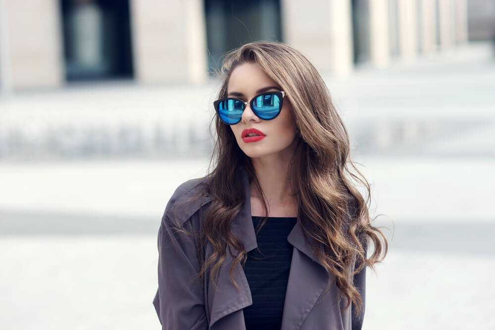 Young fashionable woman with sunglasses and soft curly hair