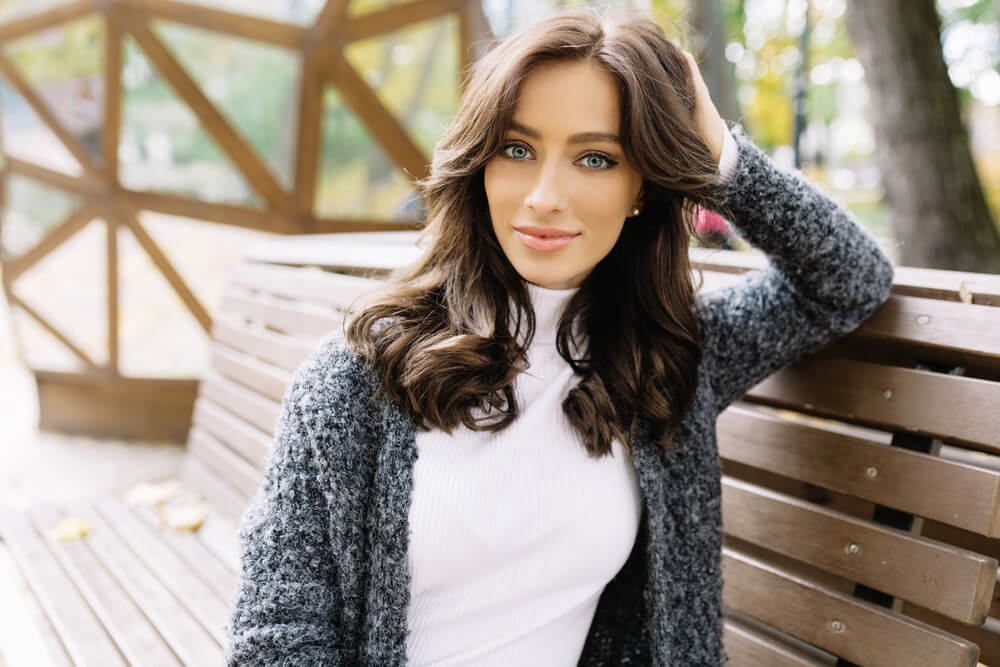 Laidback smiling woman with soft wavy hair on park bench