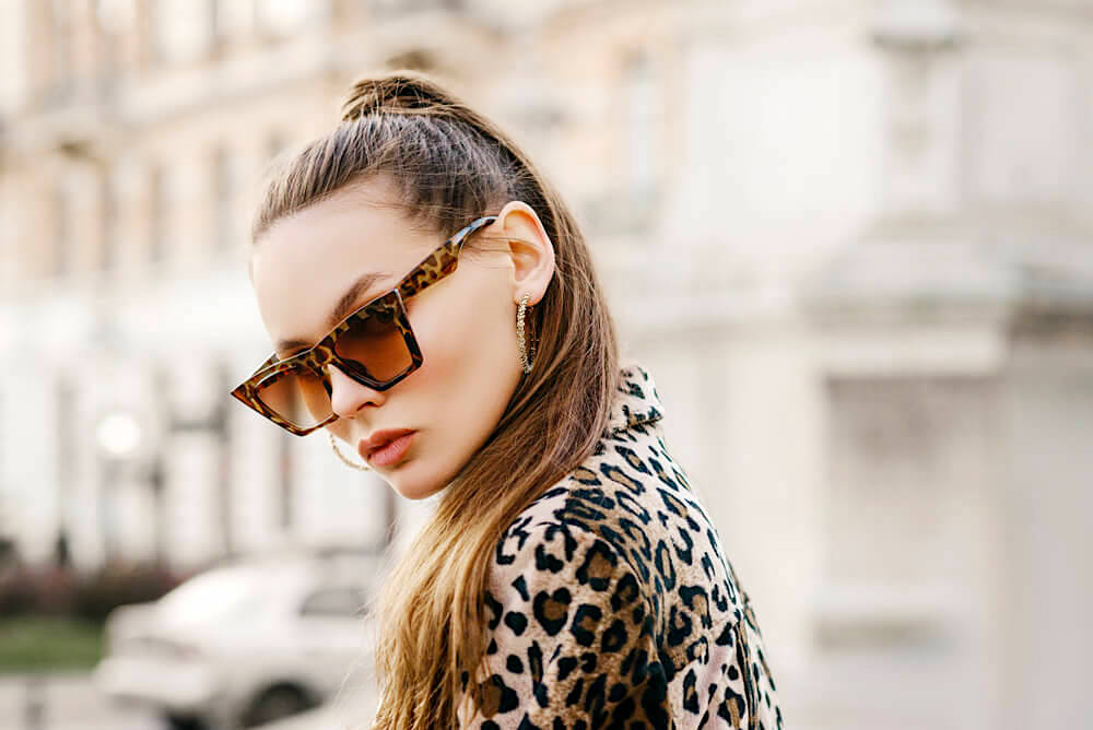 Fashionable woman in sunglasses, an animal print coat and a high ponytail