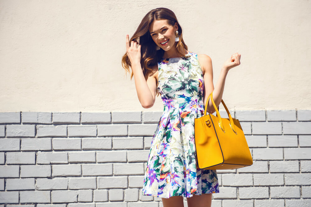 Fashionable smiling woman with middle-parted hair, a floral sun dress and a yellow handbag