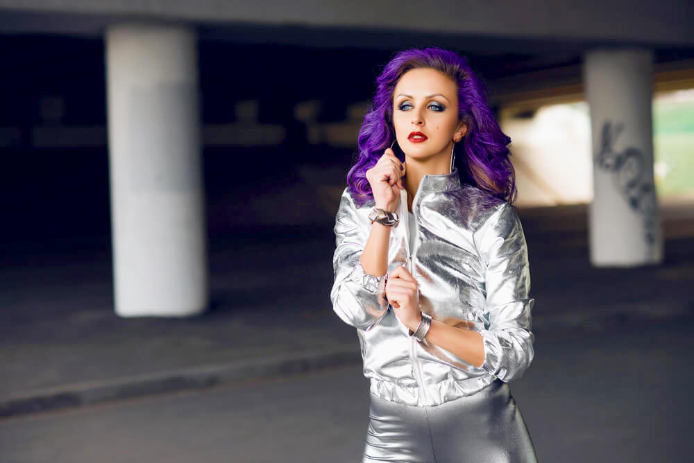 Young fashionable woman with purple hair and a silver jacket