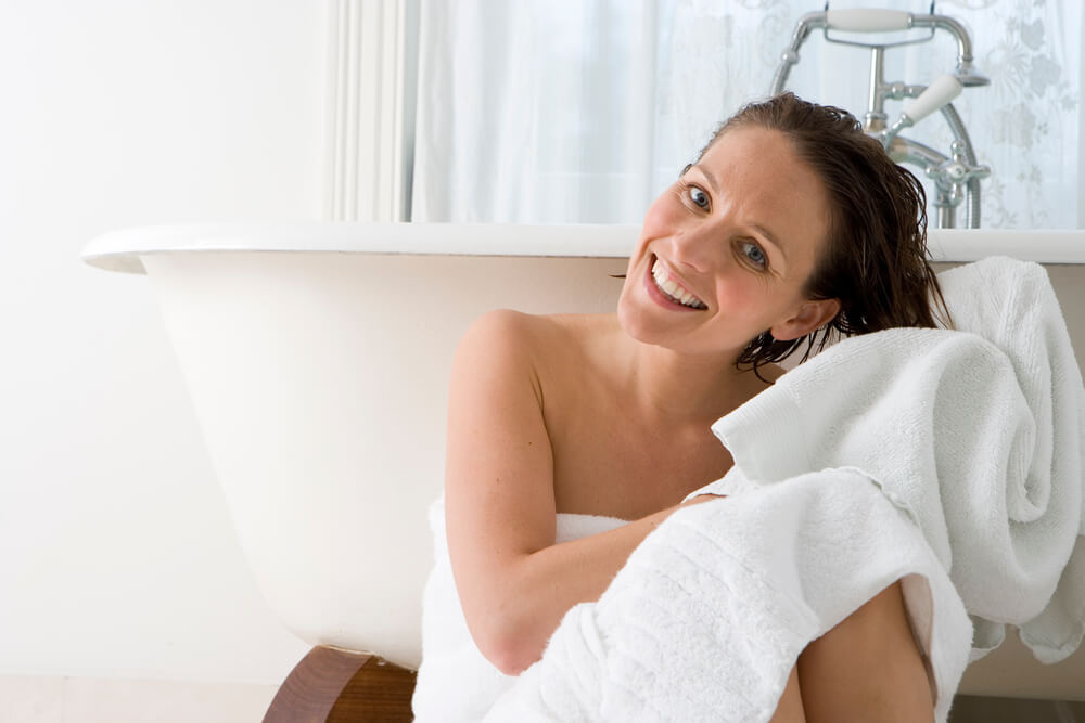 Woman rubbing wet hair with towel