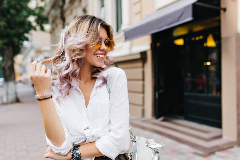Happy young blonde woman touching her hair which is dip-dyed in pink