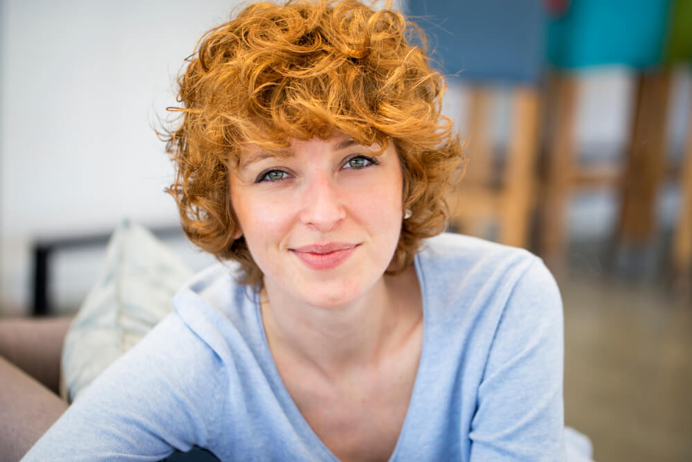 Smiling happy woman with short ginger hair