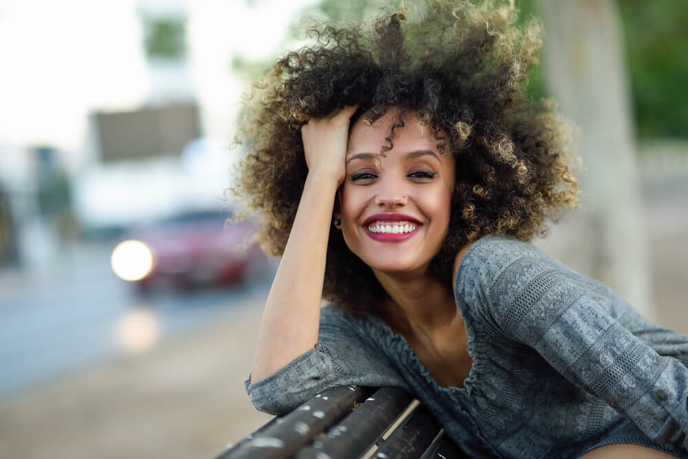 Happy smiling woman with thick afro hair dip-dyed in caramel blonde