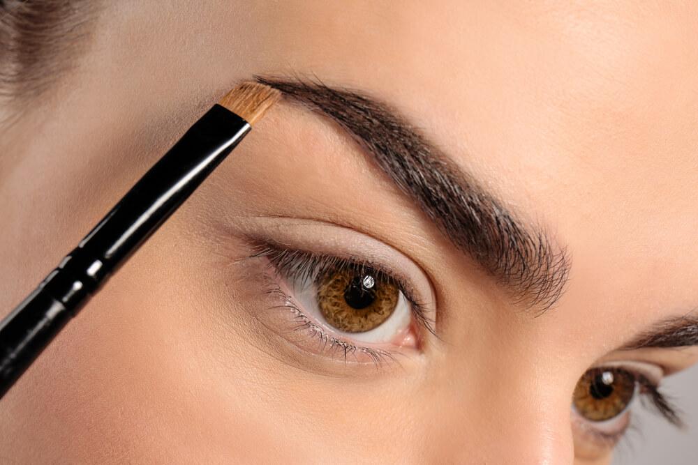 Woman using brush on eyebrows