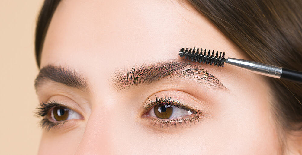 Woman with spoolie brush on brows