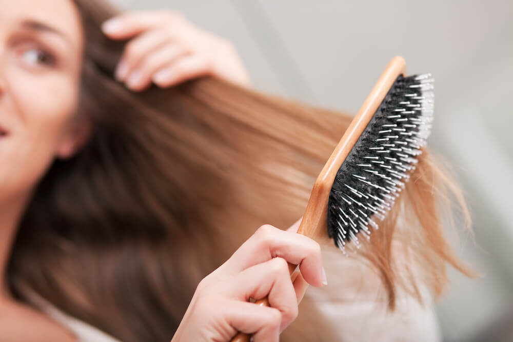 Unknown woman brushing hair with a wide-toothed brush