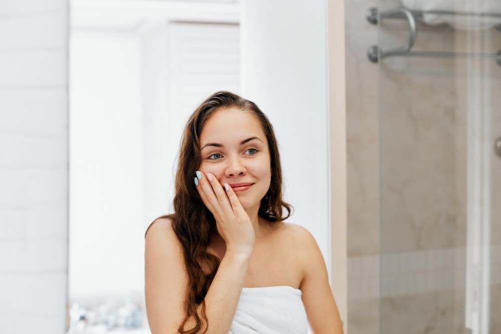 Smiling woman with freshly washed hair, looking at herself in bathroom mirror