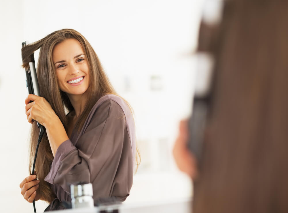 Woman curling hair with straightener