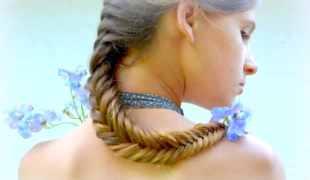 Young woman with blonde fishtail braids