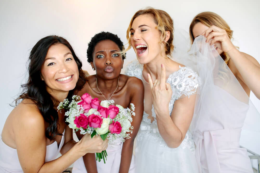 Young happy bridesmaids with a bouquet of pink flowers