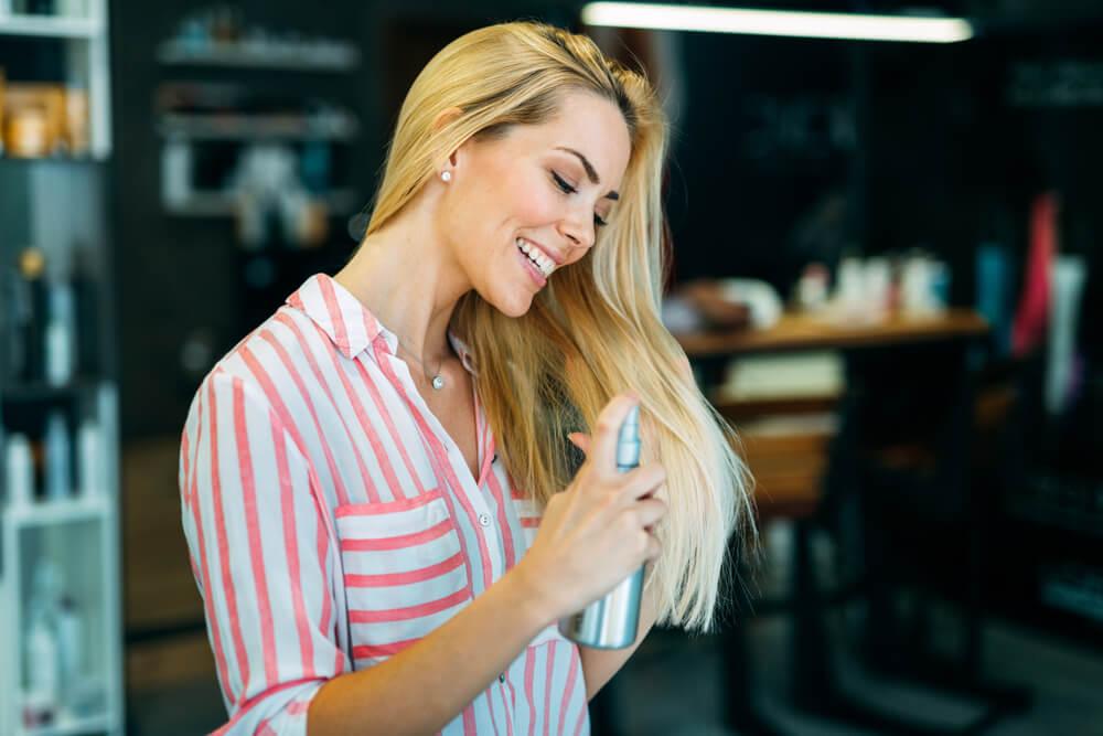 Woman adding texture spray to hair