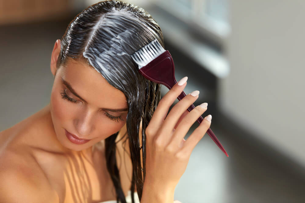 Woman applying hair mask with a brush