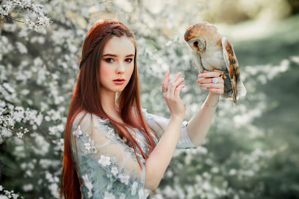 Pretty young woman with an owl on her arm