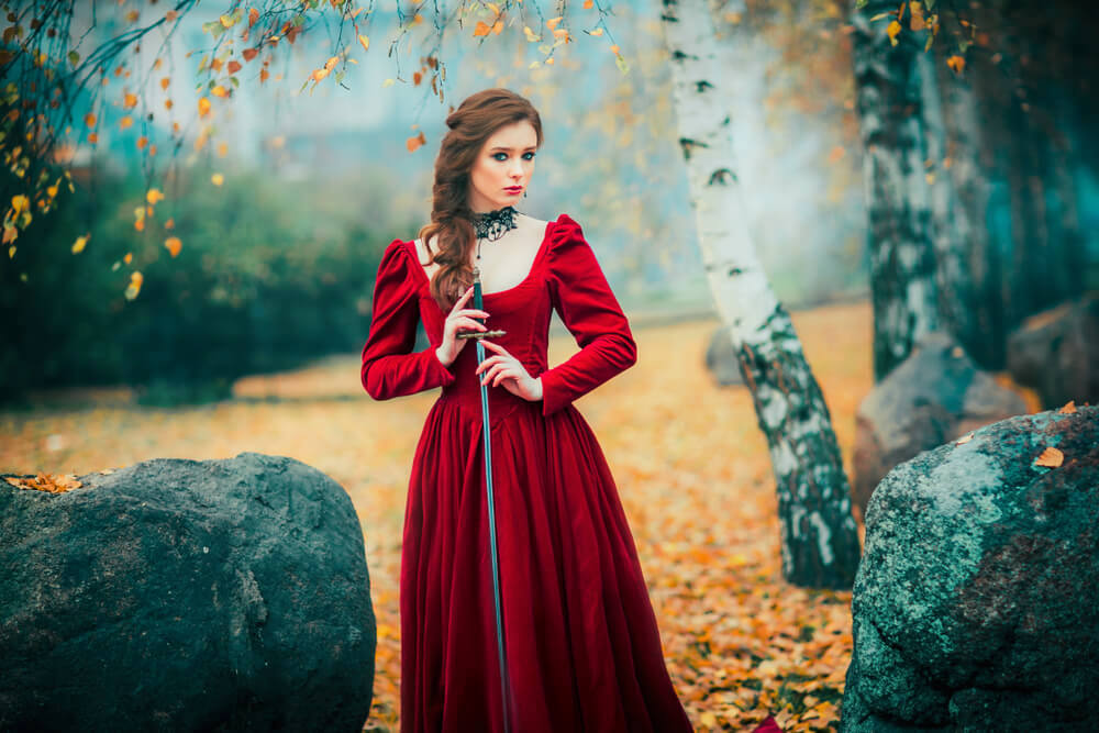 Beautiful woman with side braids, in royal red gown