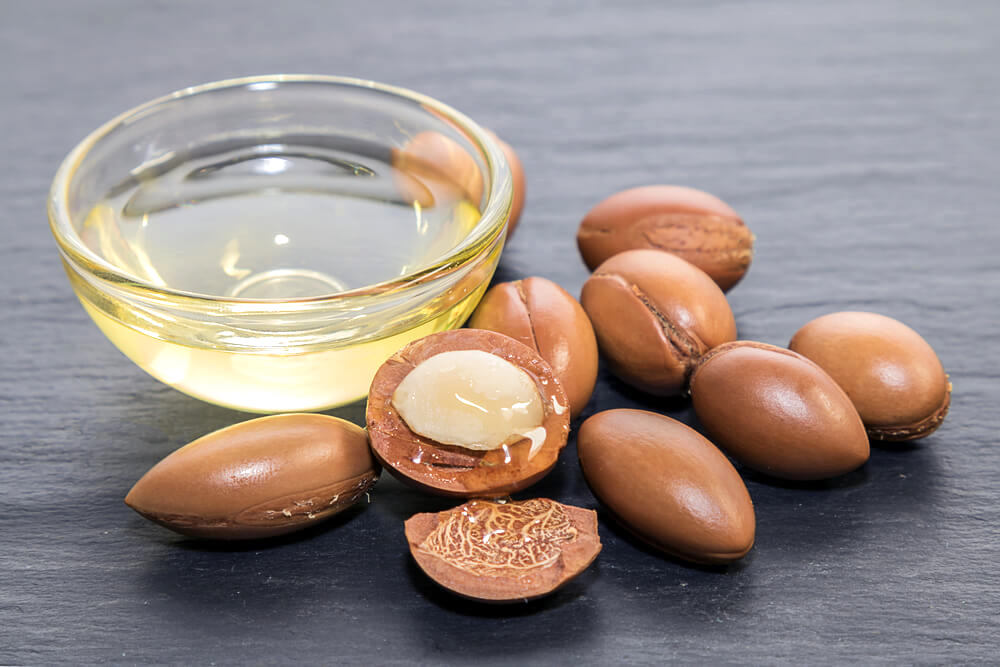 A bowl of clear oil surrounds by Argan seeds