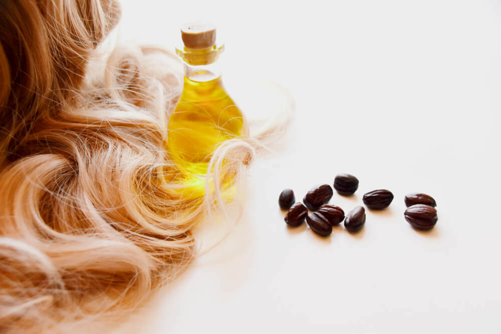 Jojoba oil and seeds with blonde hair