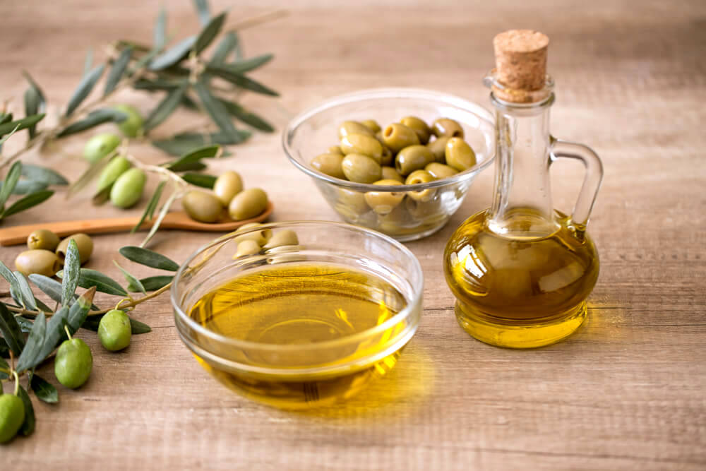Olive oil in a bowl, and fresh olives in a clear bowl