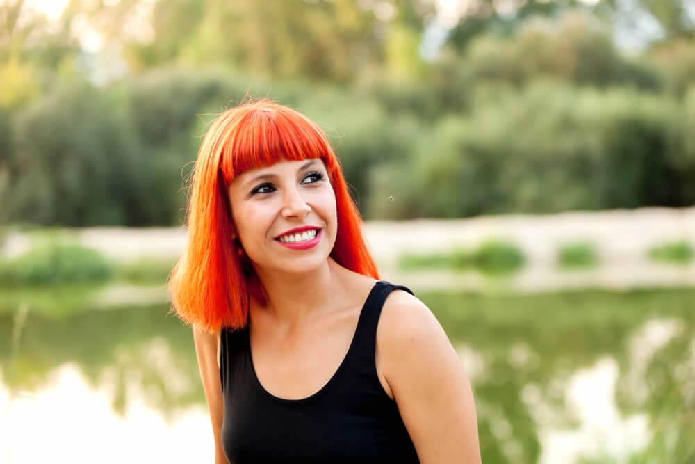 Woman with bright orange hair in the park