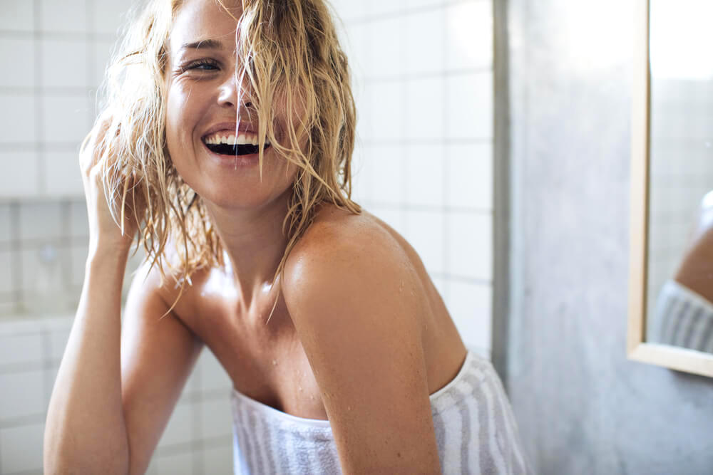 Happy woman touching wet hair in bathroom