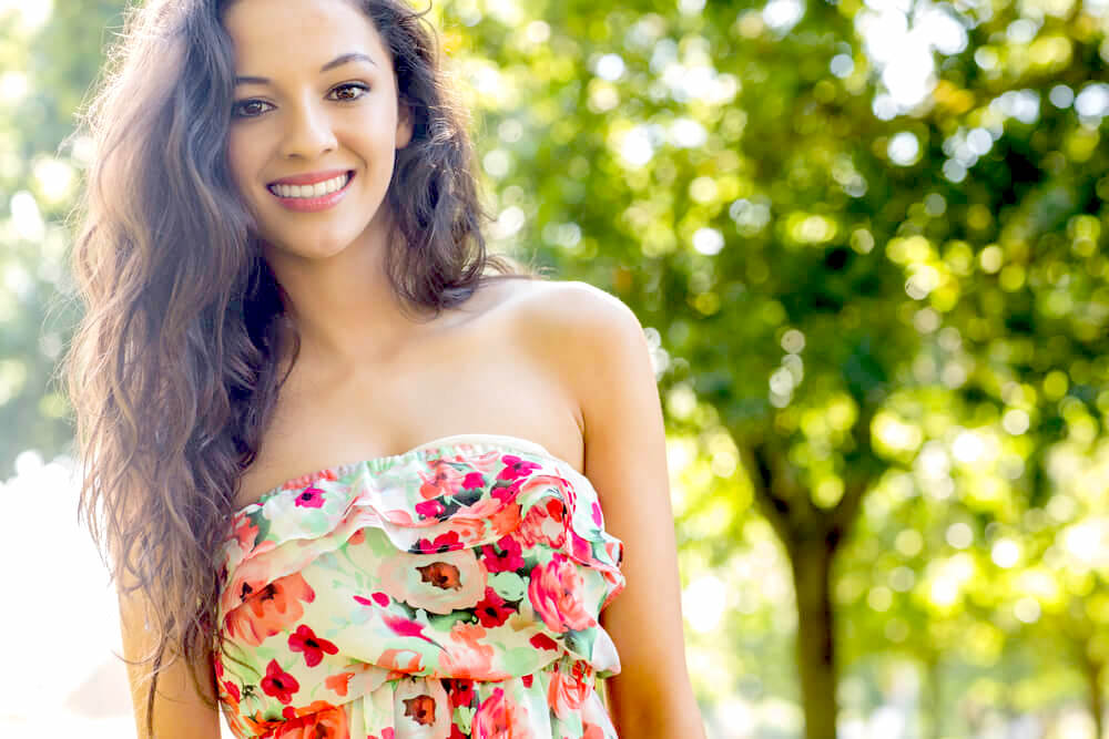 Pretty young girl in summer dress with long wavy hair