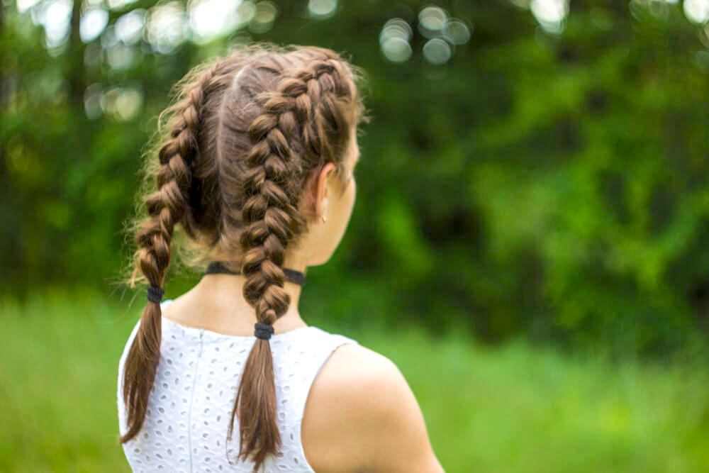 Unknown girl with double French braids out in the green fields
