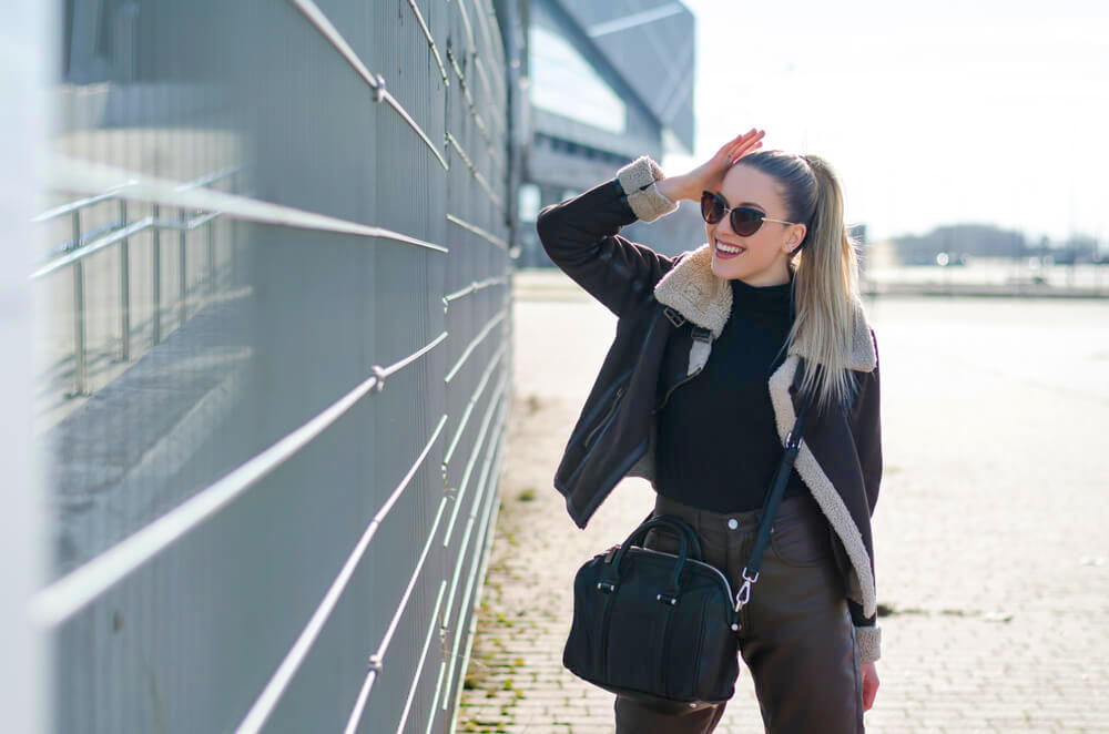 Fashionable woman in the sun and black winter clothing with high blonde ponytail